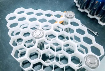 Lithium-ion battery cylinders placed within a hexagon honeycomb mesh layer.